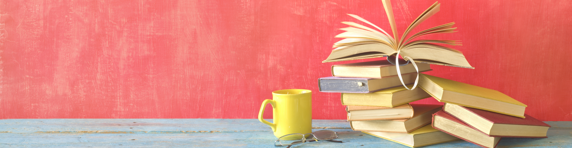 image of piled books, a mug, and reading glasses on bright pink background